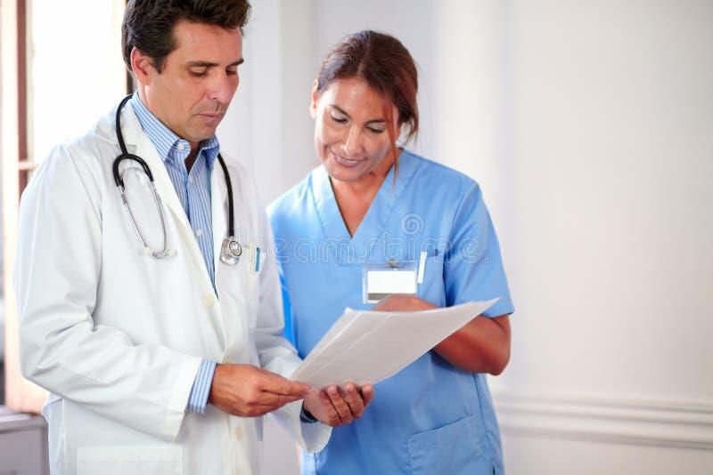 Medico ispanico bello che lavora con signora dell'infermiere immagini stock