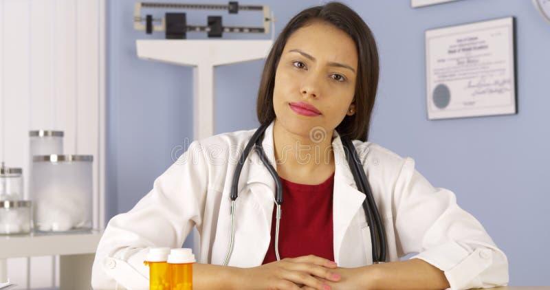 Medico ispano della donna che esamina macchina fotografica immagini stock
