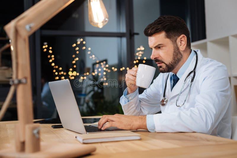 Medico lavorante duro serio che ha un turno di notte immagini stock libere da diritti