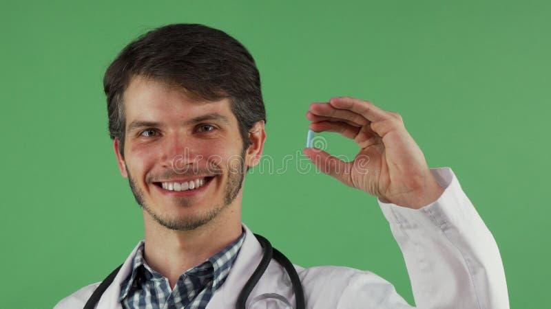 Medico maschio allegro che sorride tenendo pillola blu su fondo verde fotografia stock