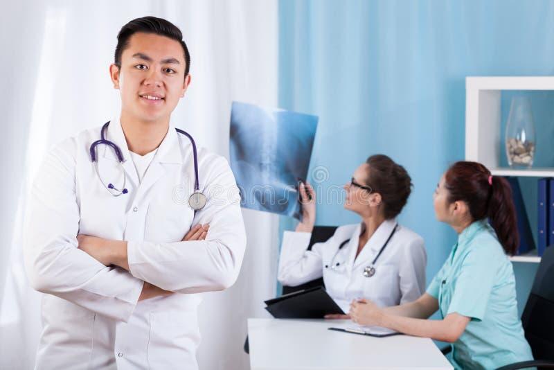 Medico maschio asiatico nell'ufficio fotografia stock