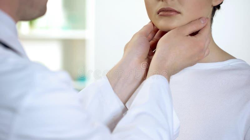 Medico maschio che controlla gola e collo pazienti, esame di salute di ospedale fotografia stock