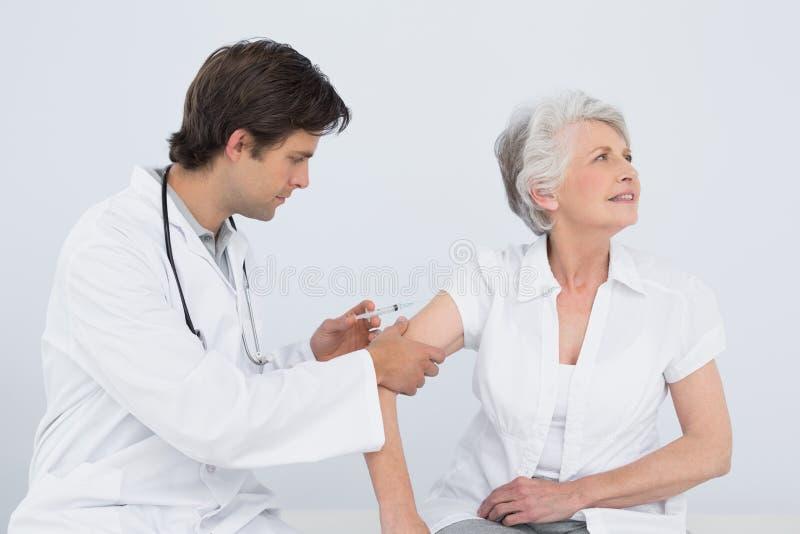Medico maschio che inietta un braccio femminile senior dei pazienti fotografia stock libera da diritti