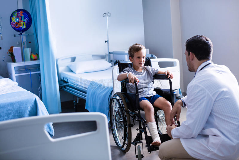 Medico maschio che interagisce con il paziente del bambino in reparto fotografia stock