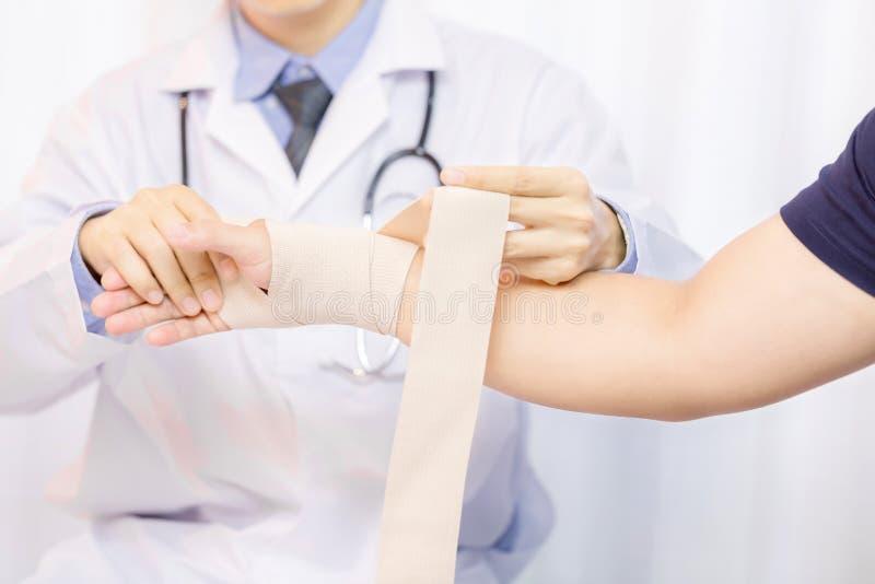 Medico maschio che mette garza sulla mano del giovane immagine stock