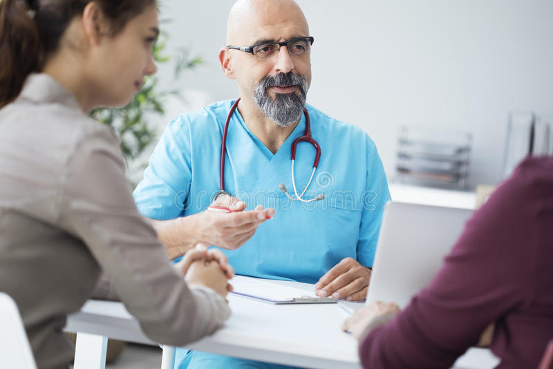 Medico maschio che parla con giovani coppie immagine stock