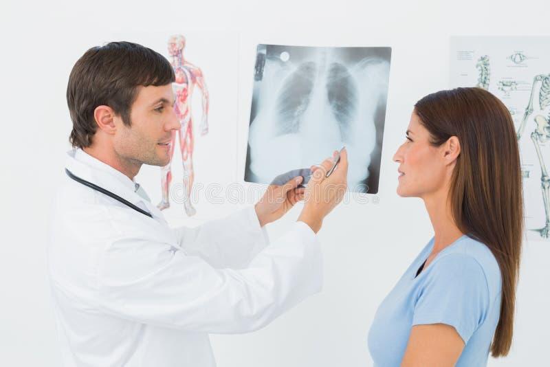 Medico maschio che spiega i raggi x dei polmoni al paziente femminile immagini stock