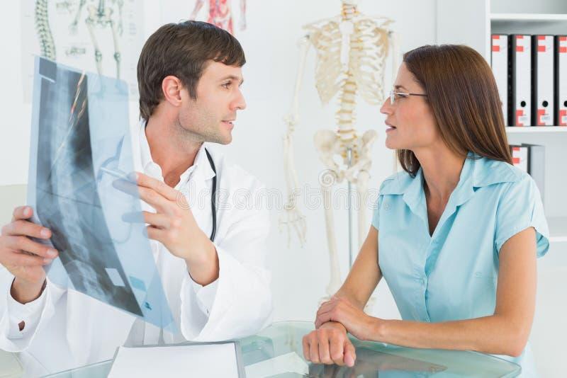 Medico maschio che spiega i raggi x della spina dorsale al paziente femminile immagine stock libera da diritti