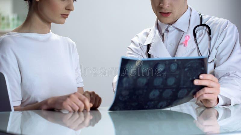 Medico maschio che spiega i risultati della giovane signora del mammogramma, consapevolezza del cancro al seno fotografia stock libera da diritti