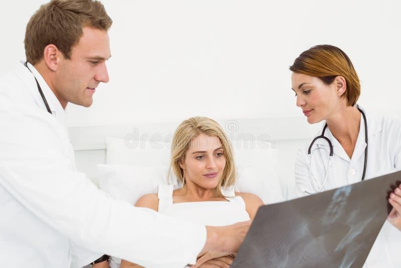 Medico maschio che spiega raggi x al paziente immagine stock