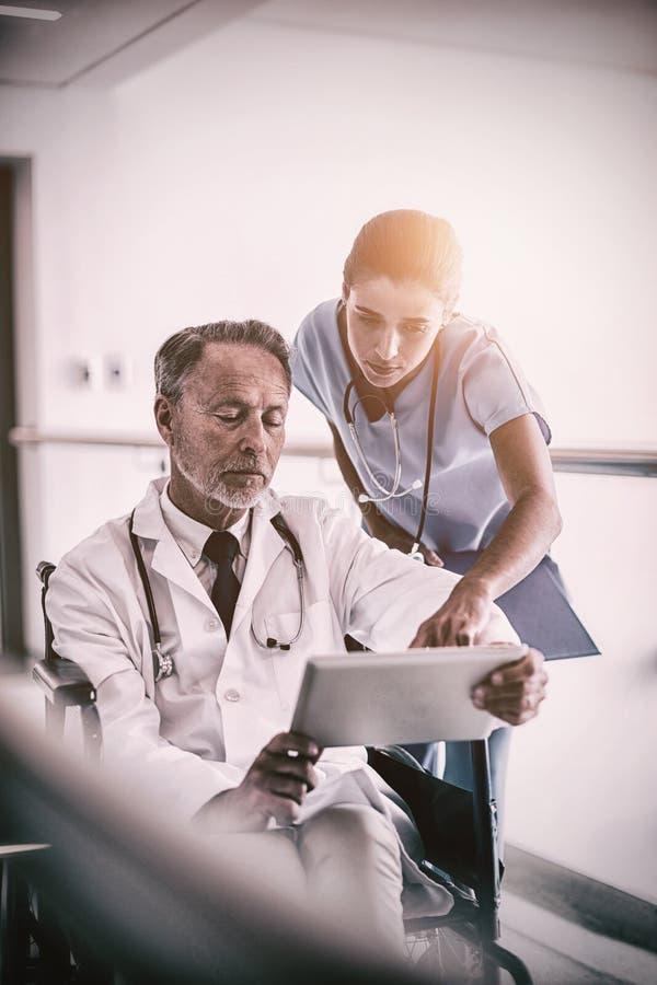 Medico maschio con l'infermiere che discute a fondo compressa digitale immagine stock libera da diritti