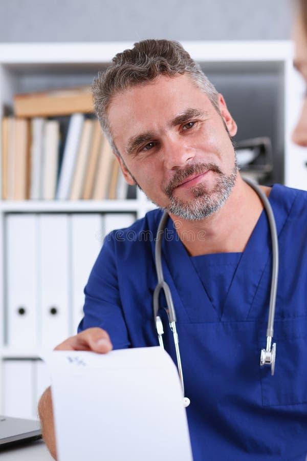 Medico maschio della medicina nella tenuta dell'uniforme del blu e nella prescrizione di elasticità fotografia stock libera da diritti