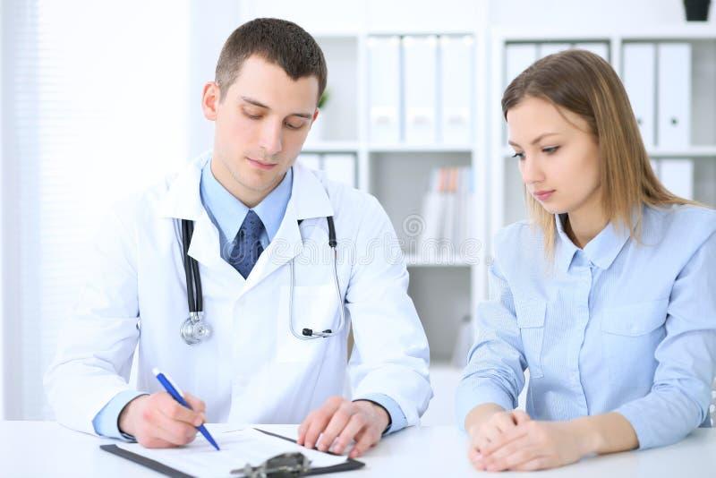 Medico maschio e paziente femminile che si siedono alla tavola in gabinetto medico fotografia stock libera da diritti