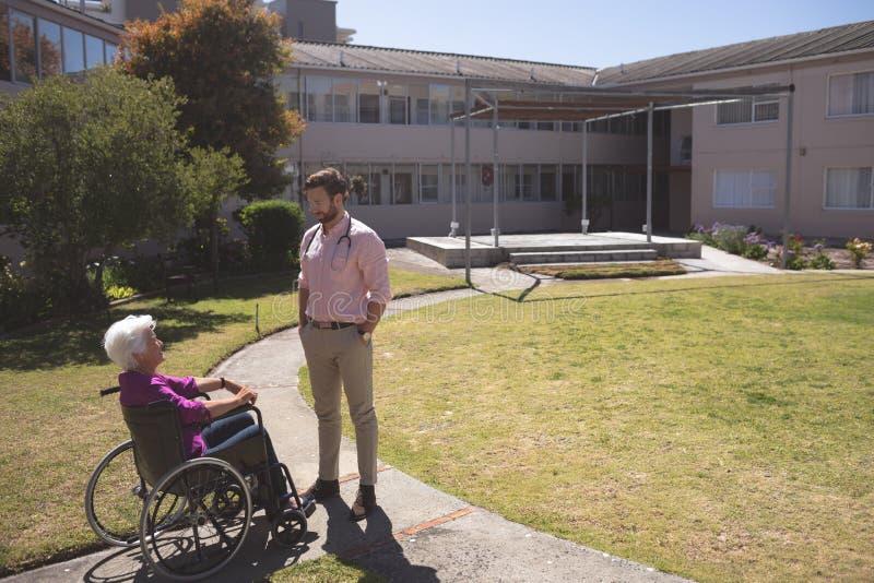 Medico maschio e paziente femminile senior che interagiscono a vicenda fotografia stock libera da diritti