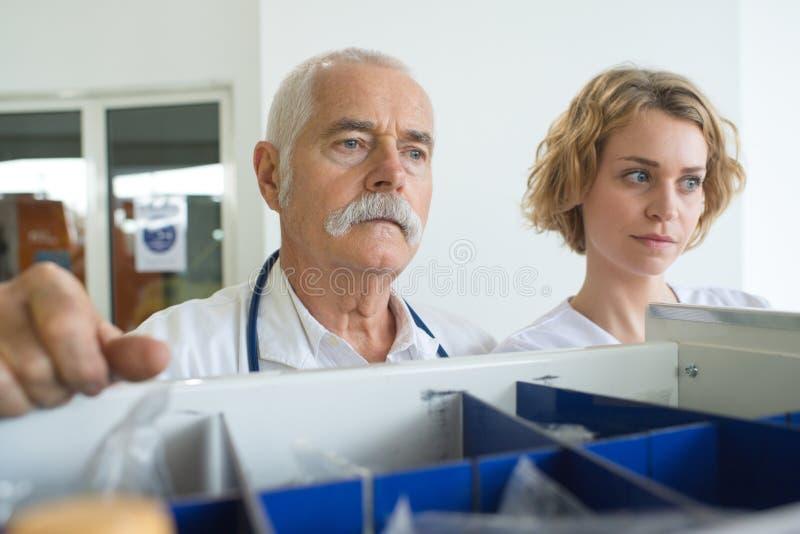 Medico maschio ed infermiere femminile nella stanza degli archivi immagine stock libera da diritti