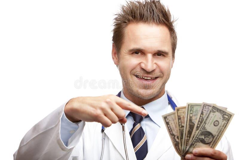 Medico maschio felice che indica a le fatture del dollaro US fotografia stock libera da diritti