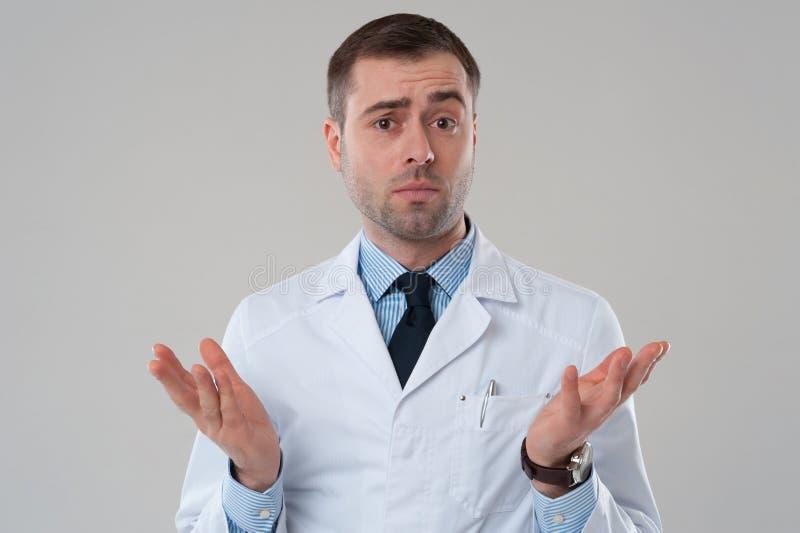 Medico maschio maturo che scrolla le spalle le spalle di sollevamento immagine stock