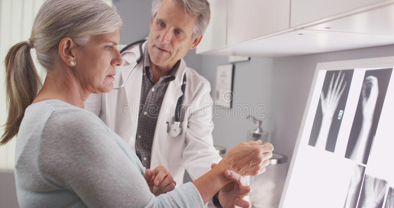 Medico maschio senior che valuta il polso fratturato del paziente fotografia stock libera da diritti