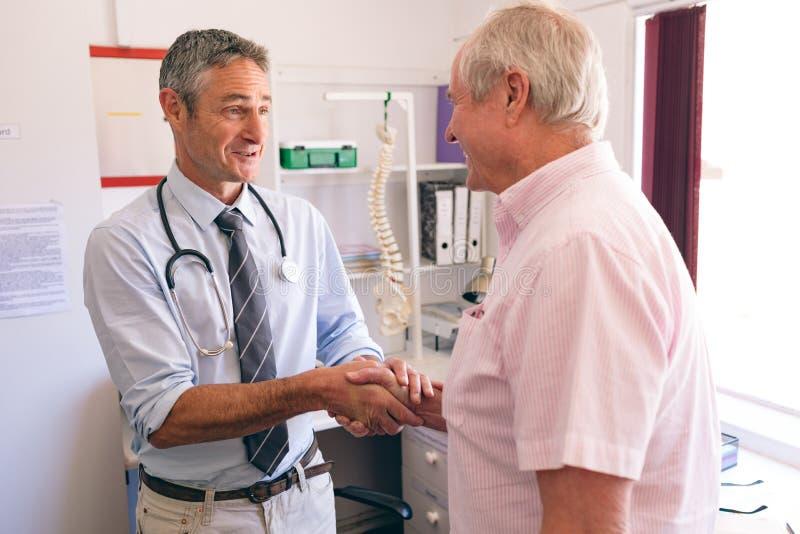 Medico maschio sicuro che interagisce con il paziente maschio senior in clinica immagini stock libere da diritti