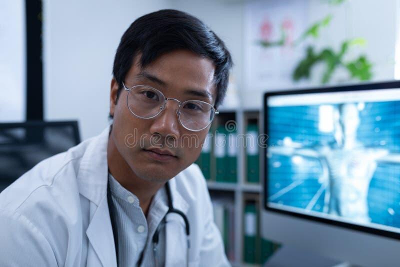 Medico maschio sicuro che si siede nella clinica all'ospedale fotografie stock