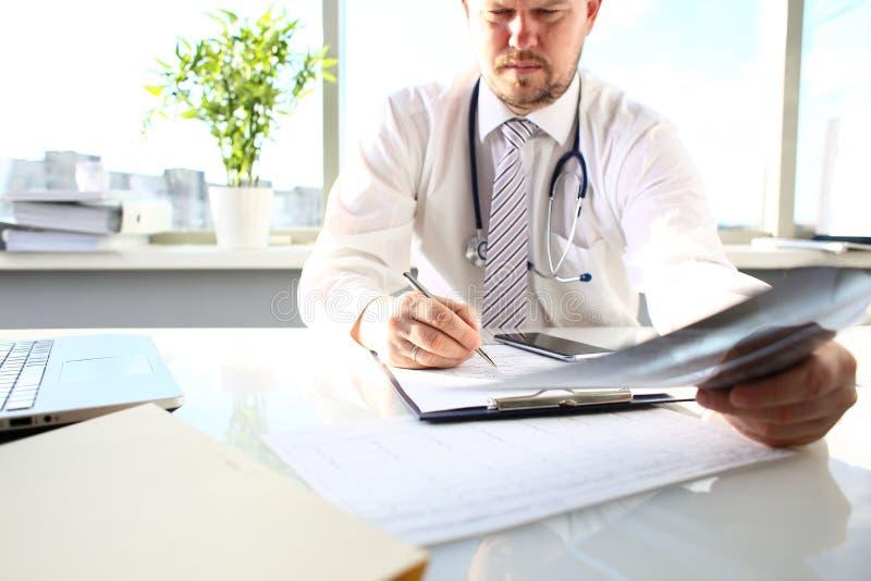 Medico maschio tiene nella penna e nello sguardo dell'argento del braccio ai raggi x fotografia stock