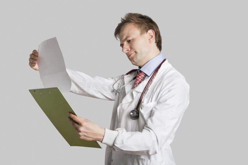 Medico maschio in un cappotto del laboratorio che legge le cartelle sanitarie sopra fondo grigio fotografia stock
