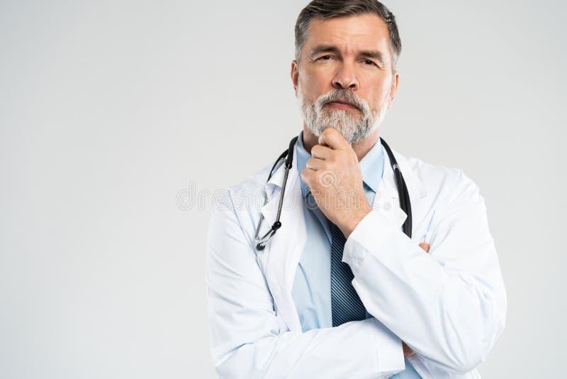 Medico maturo allegro che posa e che sorride alla macchina fotografica, alla sanit? ed alla medicina fotografia stock