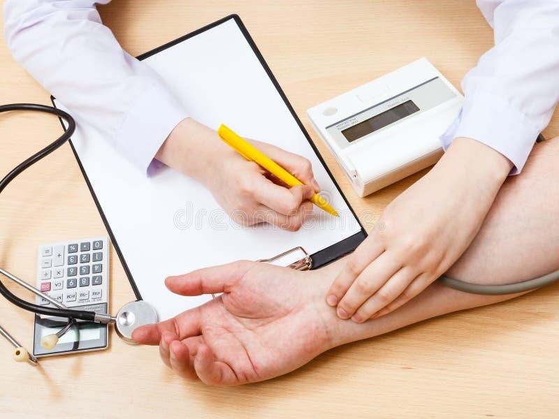 Medico misura l'impulso del sangue del paziente fotografia stock libera da diritti