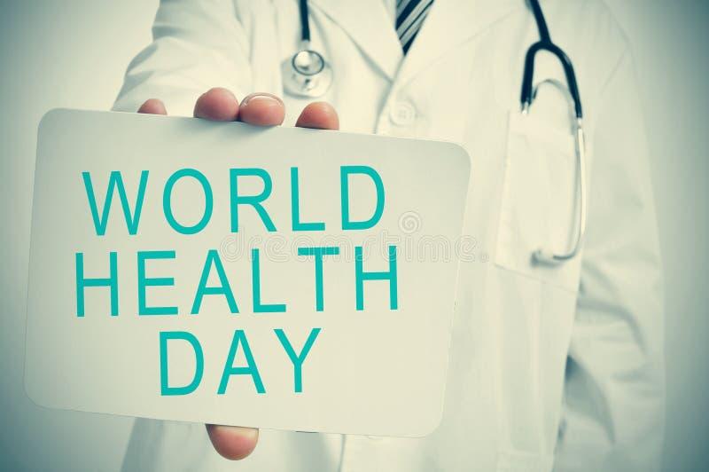 Medico mostra un'insegna con il giorno di salute di mondo del testo fotografie stock libere da diritti