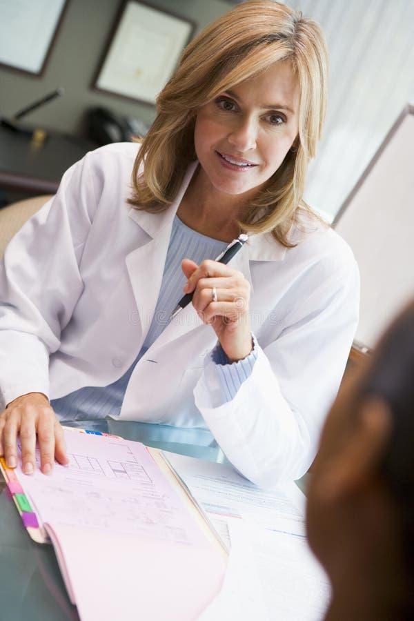 Medico nella discussione con il paziente nella clinica di IVF immagini stock