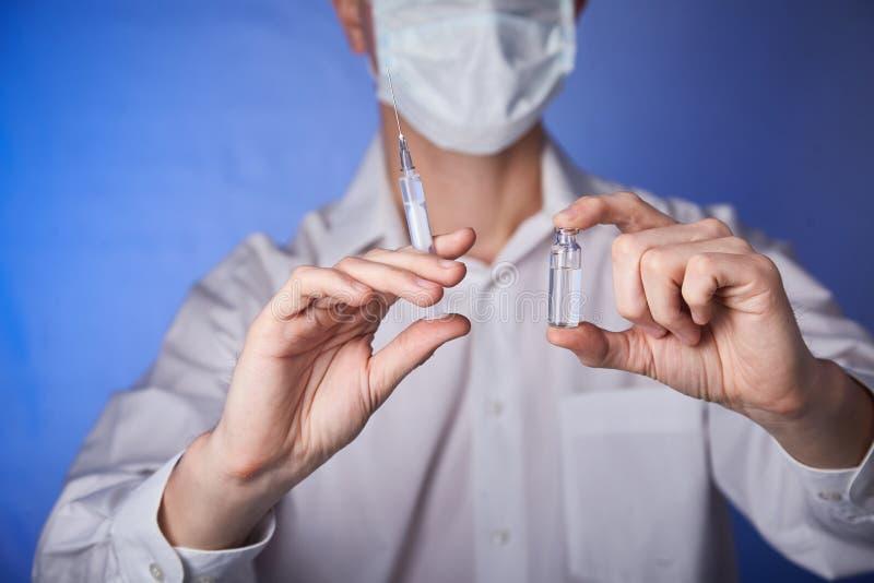 Medico nella maschera con una siringa dell'iniezione sui precedenti blu fotografia stock