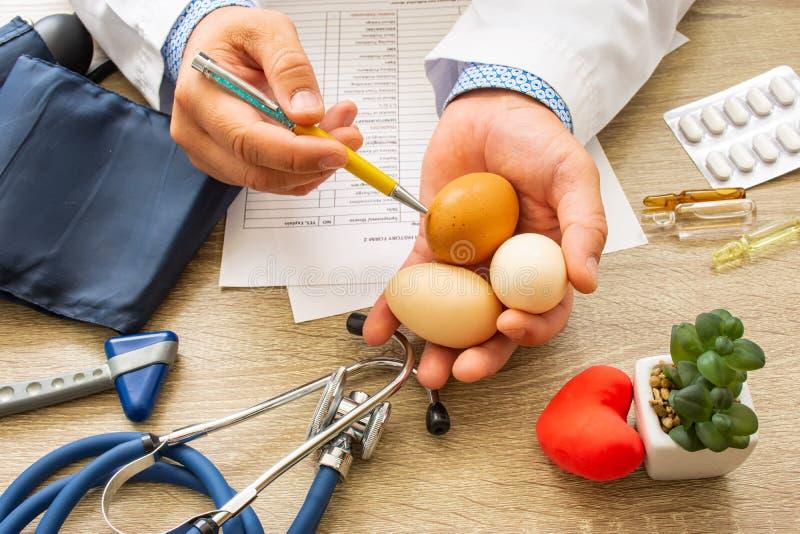 Medico nutrizionista durante la consultazione tenuto in mano e mostra le uova crude del paziente Consulenza e spiegazione dell'us fotografia stock libera da diritti