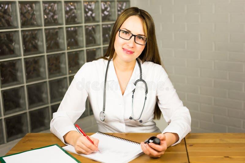Medico o farmacista femminile della medicina del medico che si siede alla tavola di lavoro, tenendo barattolo o bottiglia delle p fotografia stock