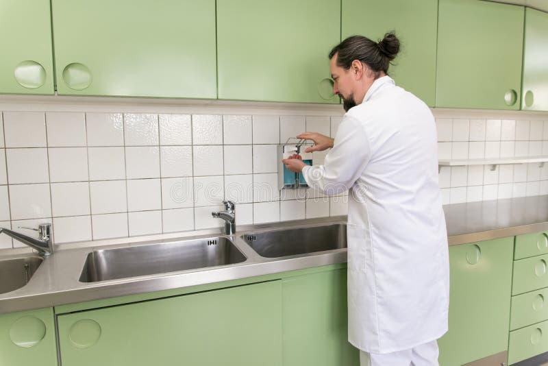 Medico o il chirurgo maschio sta disinfettando le sue mani fotografia stock