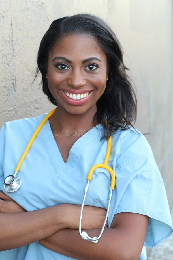 Medico o infermiere afroamericano femminile che sorride sopra il fondo scuro immagine stock
