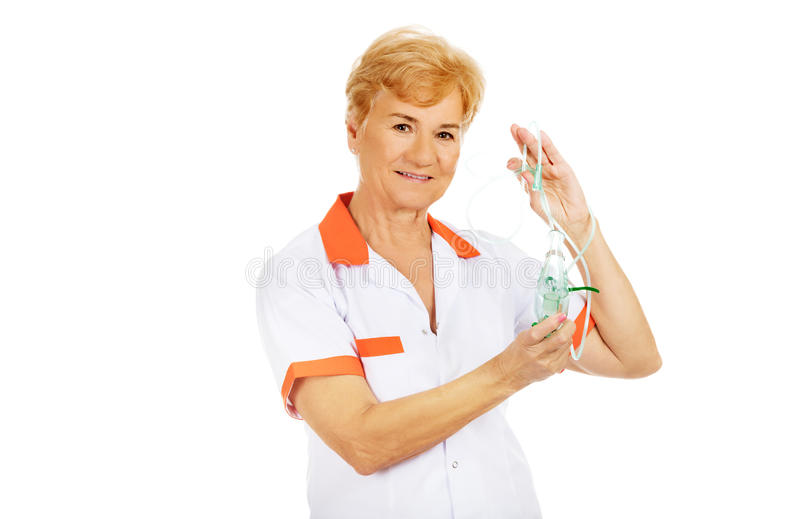 Medico o l'infermiere femminile anziano di sorriso tiene la maschera di ossigeno fotografie stock