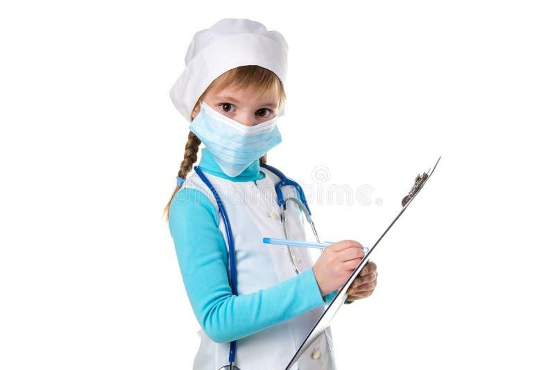 Medico o l'infermiere femminile con lo stetoscopio e la maschera scrive una nota in taccuino contro fondo bianco, esaminante immagini stock