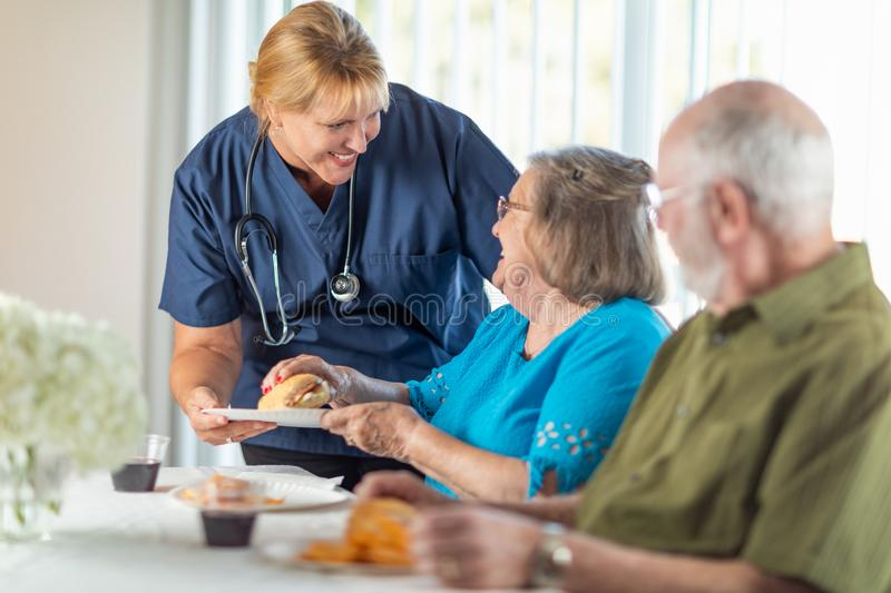 Medico o l'infermiere utile Serving Senior Adult coppia un pasto fotografia stock