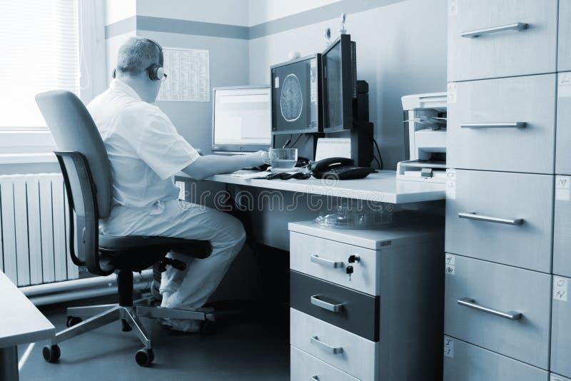 Medico ospedaliero dell'uomo con i raggi x & il computer portatile fotografia stock