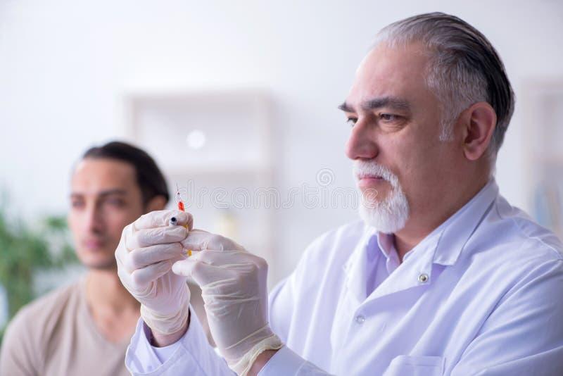 Medico paziente maschio del visitng per l'inoculazione sparata immagine stock