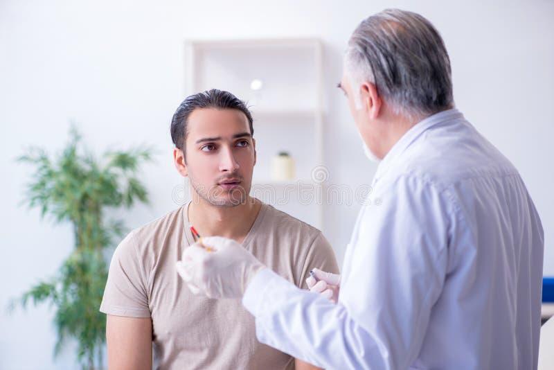 Medico paziente maschio del visitng per l'inoculazione sparata immagine stock libera da diritti