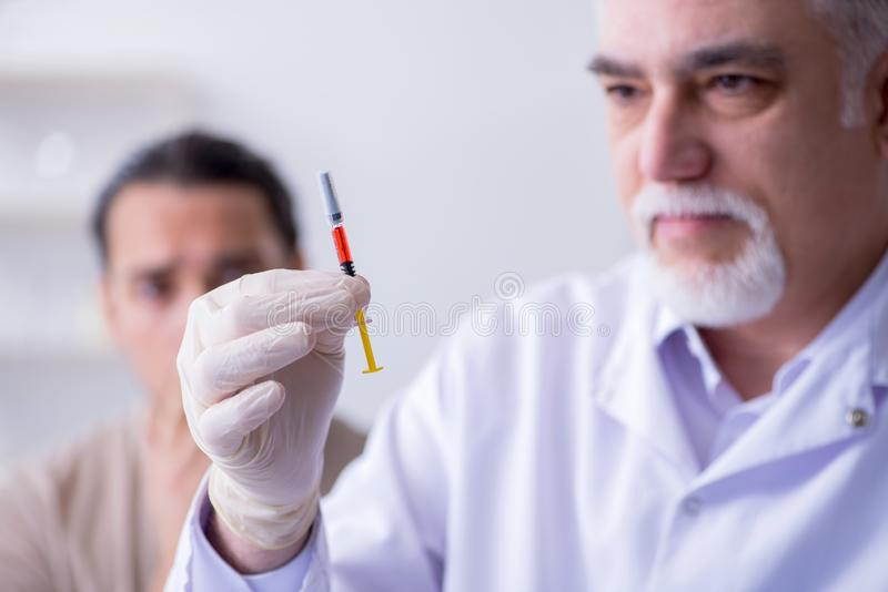 Medico paziente maschio del visitng per l'inoculazione sparata fotografia stock
