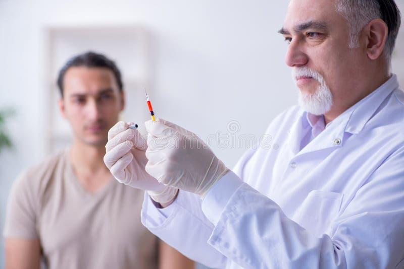 Medico paziente maschio del visitng per l'inoculazione sparata immagini stock