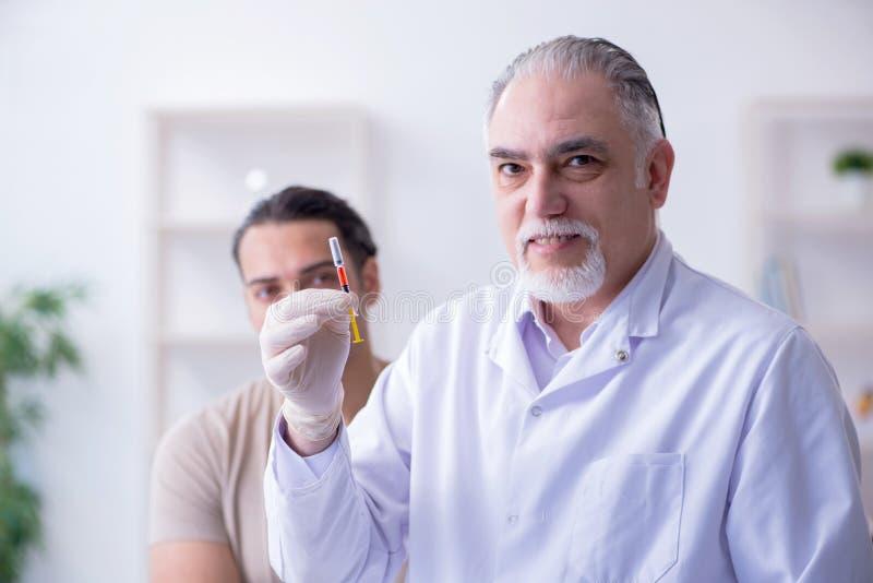 Medico paziente maschio del visitng per l'inoculazione sparata fotografia stock libera da diritti