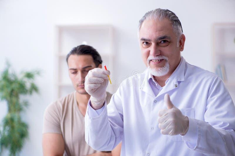 Medico paziente maschio del visitng per l'inoculazione sparata fotografie stock
