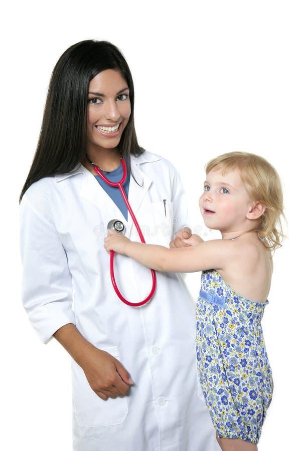 Medico pediatrico del Brunette con la bambina bionda immagini stock