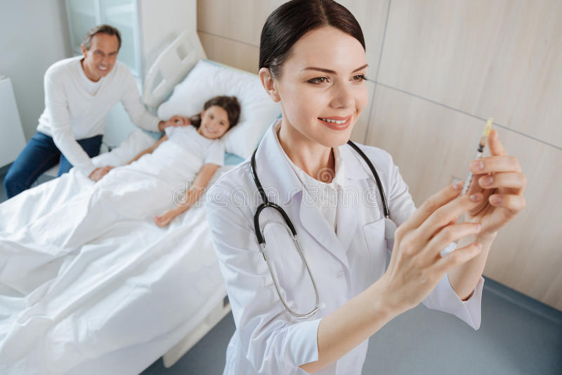 Medico positivo allegro che prepara per un'iniezione fotografie stock