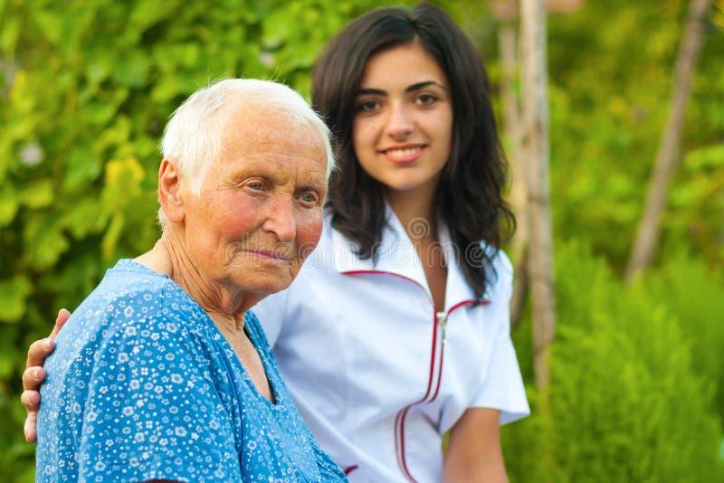 Medico preoccupantesi con la donna anziana ammalata all'aperto fotografie stock