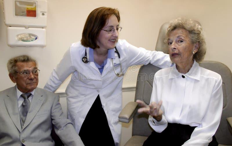 Medico preoccupantesi ed i suoi pazienti immagini stock
