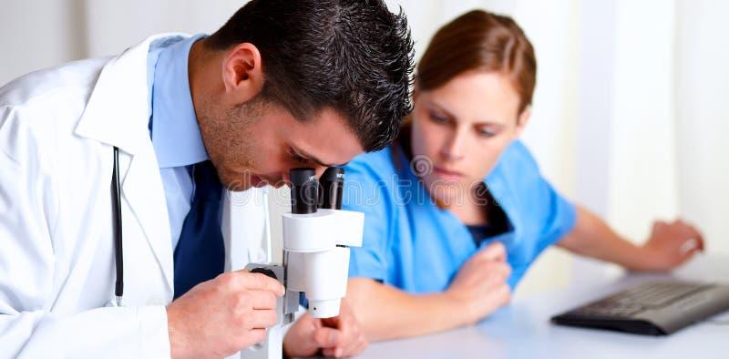 Medico professionale bello per mezzo di un microscopio fotografie stock libere da diritti